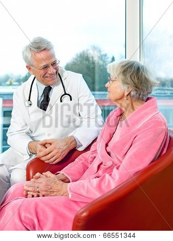 Friendly Senior Male Doctor Chatting To A Patient