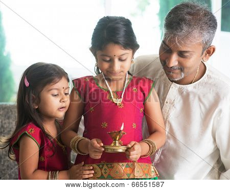 Indian family in traditional sari celebrate diwali or deepavali at home. Little girl hands holding oil lamp during festival of light.