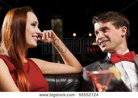 Young handsome man in restaurant accompanied by elegant lady