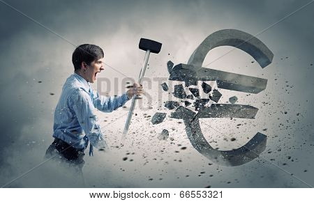 Young businessman crashing with hammer stone euro symbol