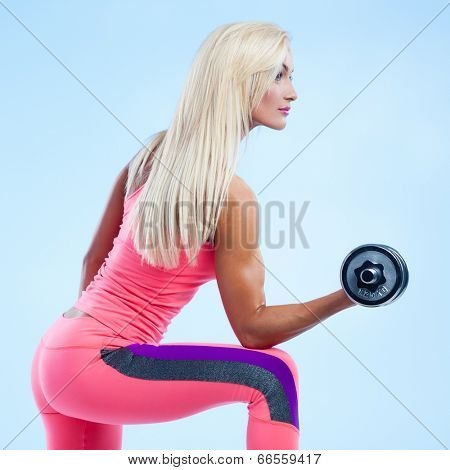 Beautiful fitness model posing with dumbbells on blue background