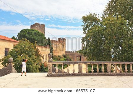 TOMAR, PORTUGAL - SEPTEMBER 29, 2011: The imposing medieval castle - the monastery of the Templars. Woman dressed in white photographs in the park