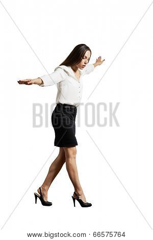 businesswoman walking on invisible line. isolated on white background