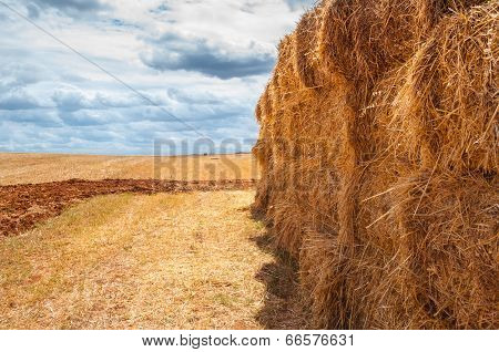 straw bales over mown field, cloud cover