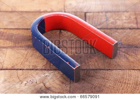 Magnet on color wooden background