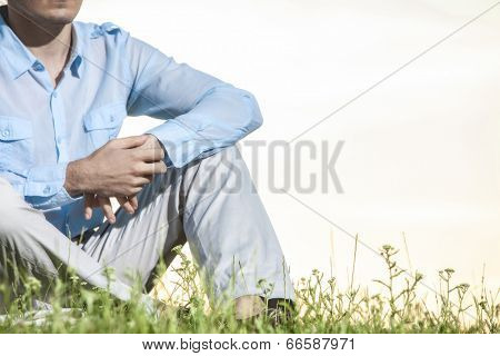 Midsection of man sitting on grass against clear sky