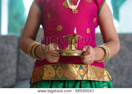 Diwali or deepavali photo with little girl hands holding oil lamp during festival of light.
