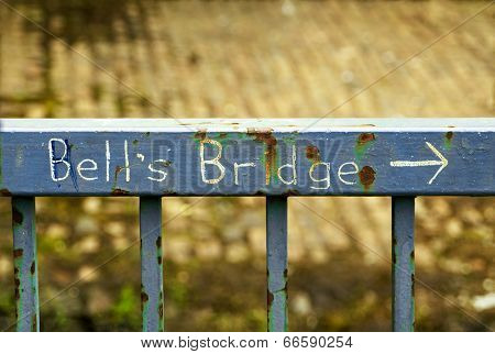Handwritten Sign On A Rusty Fence Indicating The Direction To Bell's Bridge