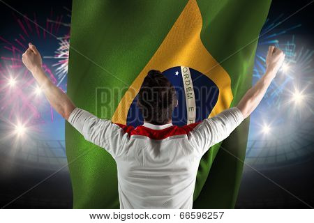 Excited football fan cheering against fireworks exploding over football stadium and brasil flag