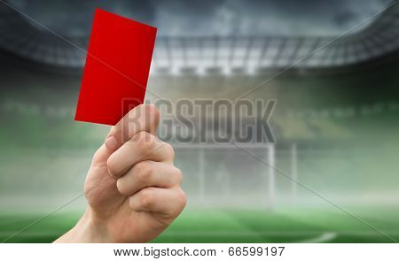 Hand holding up red card against football pitch in large stadium