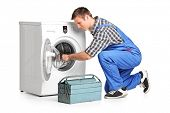 stock photo of jumpsuits  - Young plumber fixing a washing machine isolated on white background - JPG