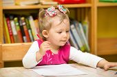 foto of little young child children girl toddler  - Child girl drawing with colorful pencils in preschool at the table - JPG