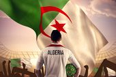 foto of algeria  - Algeria football player holding ball against large football stadium under bright blue sky - JPG