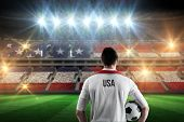 stock photo of football pitch  - Usa football player holding ball against stadium full of usa football fans - JPG