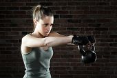 foto of kettles  - Portrait of Young fit woman lifting kettle bell - JPG