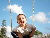 picture of swingset  - young happy boy playing on outdoor swing set