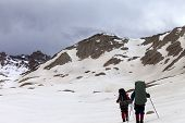 stock photo of plateau  - Two hikers on snowy plateau before storm - JPG
