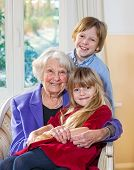 stock photo of babysitting  - Portrait of an elderly grandmother and her grandchildren sitting in an armchair with the little girl on her lap while her young brother stands behind all looking at the camera with lovely happy smiles - JPG