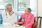 picture of sphygmomanometer  - Doctor taking an elderly womans blood pressure with a sphygmomanometer or pressure cuff as they sit talking during a consultation in the clinic - JPG