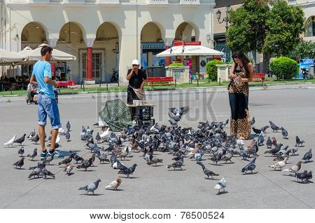 Young Man And Woman Are Feeding Pigeons In The Square Of Aristotle, Thessaloniki, Greece