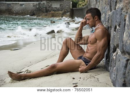 Solitary Athletic Young Man On The Beach Listening To Music