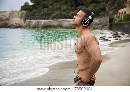 Handsome Muscular Young Man On The Beach With Headphones