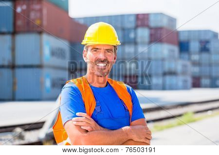 Worker standing in front of row of containers on port or yard of shipment company
