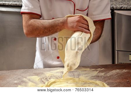 Cook preparing pizza dough.