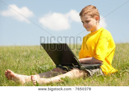 Smart Boy With A Laptop On The Grass