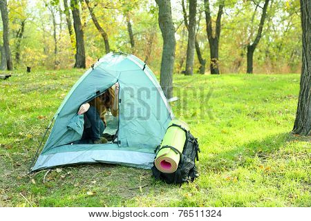 Woman opened touristic tent on green grass in a forest