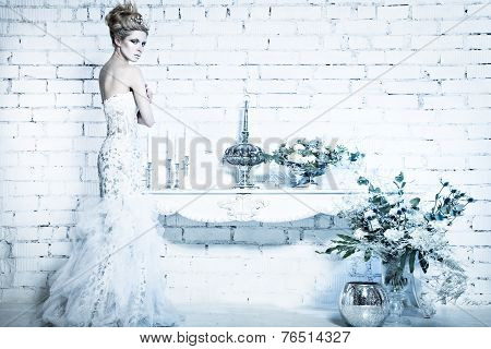 Beautiful girl in white dress in the image of the Snow Queen with a crown on her head