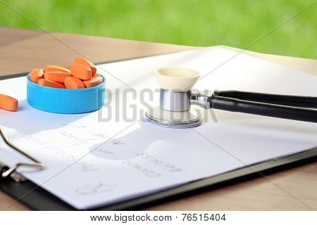Orange Pills,  Prescription And Phonendoscop On A Green  Background