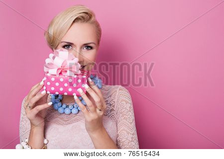 Happy birthday. Sweet blonde woman holding small gift box with ribbon. Soft colors