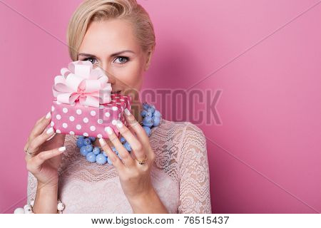 Merry christmas. Beautiful blonde woman holding small gift box with ribbon. Soft colors