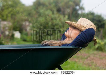 Pretty blonde napping in wheelbarrow at home in the garden