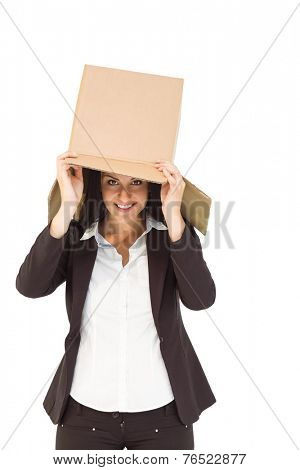 Businesswoman lifting box off head on white background
