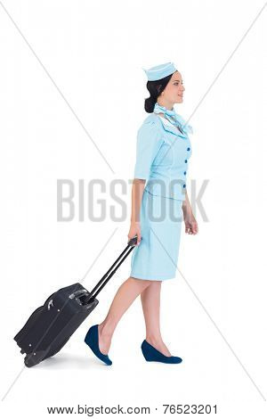 Pretty air hostess walking with suitcase on white background