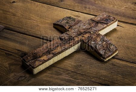 Old cross on wooden background for mourning or death concepts.