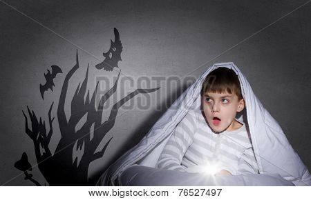Little scared boy in bed under blanket with flashlight