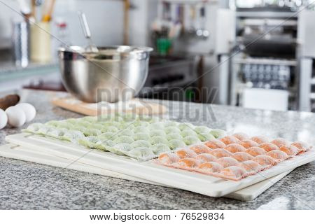 Raw ravioli pasta arranged on cutting board with ingredients at countertop in commercial kitchen