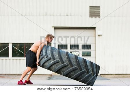 Full length side view of young male athlete flipping large tire outside gym