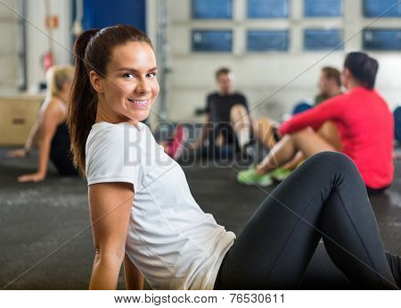 Portrait of smiling young woman exercising in cross training box