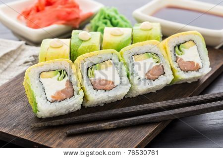 Sushi roll covered with avocado