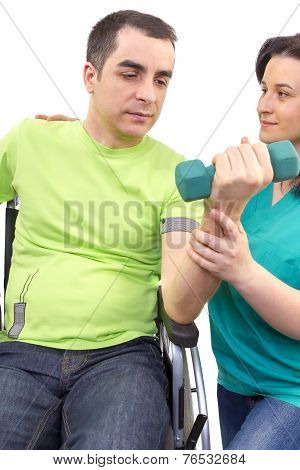 Physical Therapist Works With Patient In Lifting Hands Weights