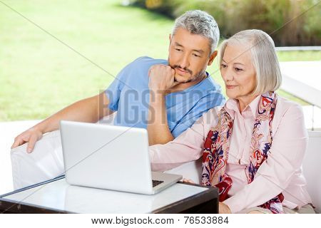 Male caretaker and senior woman using laptop while sitting on couch at nursing home