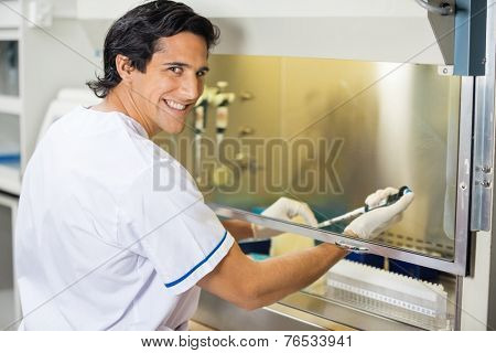 Portrait of happy male technician experimenting in laboratory