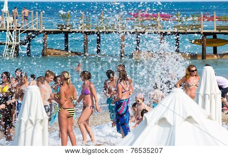Kemer, Turkey-August 21, 2014. Foam Party on resort. Group of people enjoying in drinking, dancing a