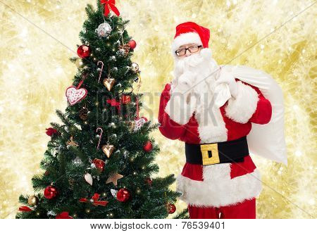 christmas, holidays and people concept - man in costume of santa claus with bag and christmas tree making hush gesture over yellow lights background