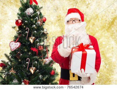 christmas, holidays and people concept - man in costume of santa claus with gift box and tree making hush gesture over yellow lights background
