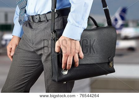 Businessman Walking And Holding  A  Leather Briefcase In His Hand. Airport  Behind